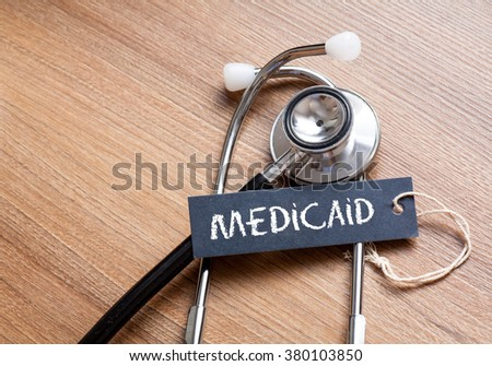 Medical Concept-Medicaid word written on label tag with Stethoscope on wood background - stock photo