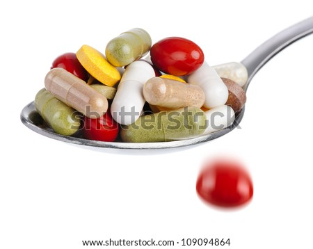Medical concept: spoon piled with colorful pills, with one tablet falling down, isolated on white - stock photo