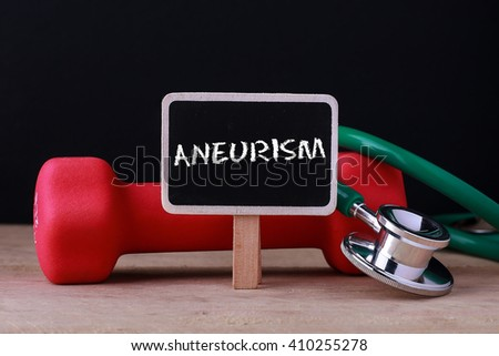 Medical concept - Stethoscope and dumbbell on wood with Aneurysm words - stock photo