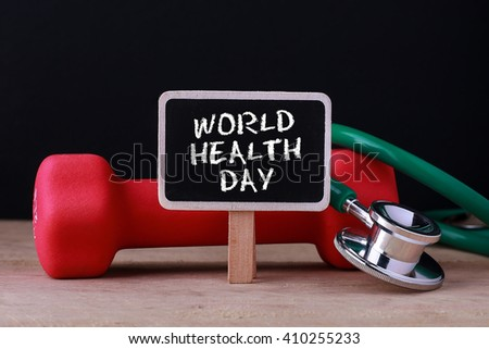 Medical concept - Stethoscope and dumbbell on wood with World Health Day words