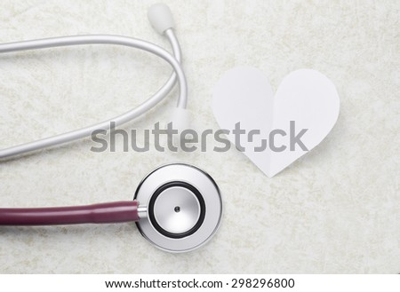medical concept Stethoscope and paper heart on table background