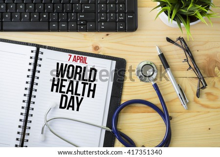 Medical Concept - Stethoscope with notebook written 7 April World Health Day with keyboard, green plant, a pen and spectacle on wooden background - stock photo