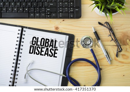 Medical Concept - Stethoscope with notebook written Global Disease with keyboard, green plant, a pen and spectacle on wooden background - stock photo