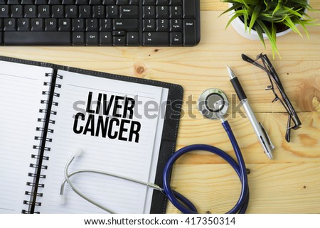 Medical Concept - Stethoscope with notebook written Liver Cancer with keyboard, green plant, a pen and spectacle on wooden background - stock photo