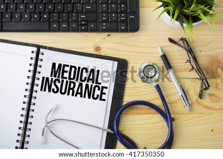 Medical Concept - Stethoscope with notebook written Medical Insurance with keyboard, green plant, a pen and spectacle on wooden background - stock photo