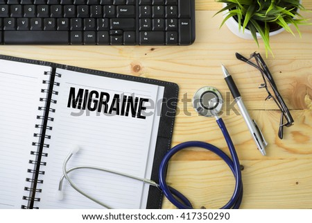 Medical Concept - Stethoscope with notebook written Migraine with keyboard, green plant, a pen and spectacle on wooden background - stock photo
