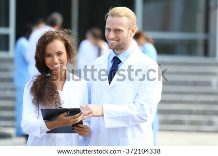 Medical concept - two doctors with stethoscopes and prescription clipboard - stock photo