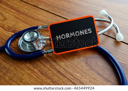 Medical concept.Word HORMONES with stethoscope on wooden table.