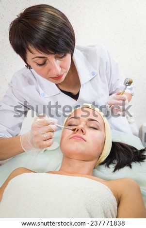 Medical cosmetic procedure. Mikronidling. Beautician performs Dermaroller procedure.young beautiful woman having an injection mesotherapy.osmetic procedures in spa clinic. - stock photo