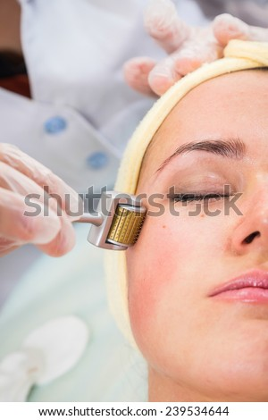 Medical cosmetic procedure. Mikronidling. Beautician performs Dermaroller procedure.young beautiful woman having an injection mesotherapy.Cosmetic procedures in spa clinic. - stock photo