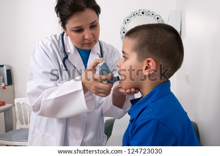 Medical doctor applying oxygen treatment on a little boy with asthma - stock photo
