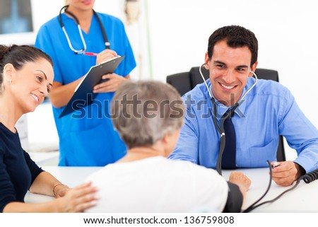 medical doctor checking senior patient's blood pressure - stock photo