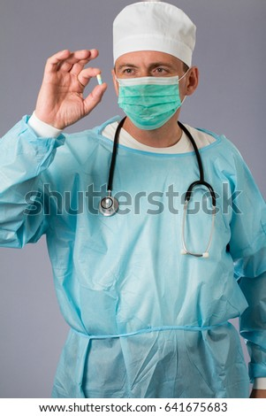 Medical doctor dressed in a medical gown with stethoscope and face mask holding a pill. Grey background