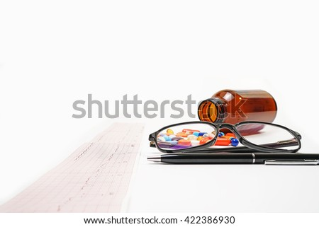 Medical Doctor.Electrocardiogram ecg heart beat test in paper ,medicine,bottle,glasses,pen isolated on white background. - stock photo