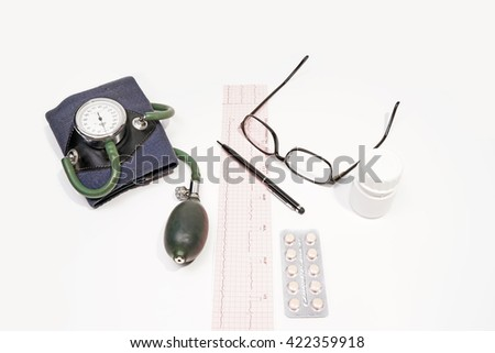Medical doctor.Electrocardiogram Result ,medicine,bottle ,vintage sphygmomanometer ,glasses,pen,isolated on the white background. - stock photo
