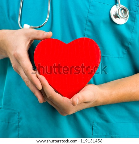 medical doctor holding a heart symbol  on white background