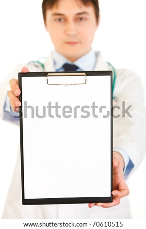 Medical doctor holding blank clipboard in hand isolated on white. Close-up. - stock photo