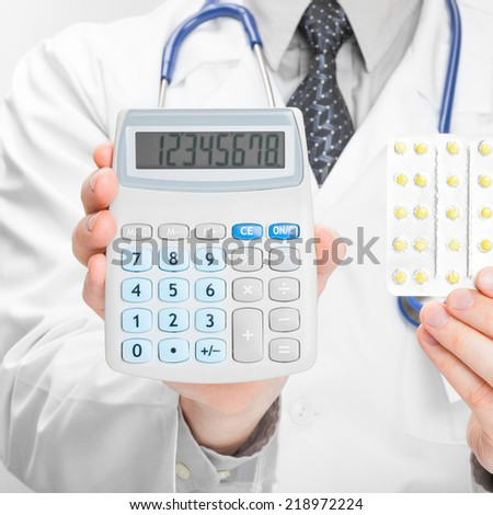 Medical doctor holding calculator and pills in his hands - 1 to 1 ratio - stock photo