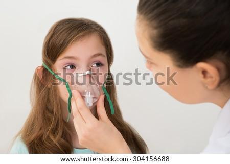 Medical Doctor Holding Inhaler Mask For Girl Breathing - stock photo