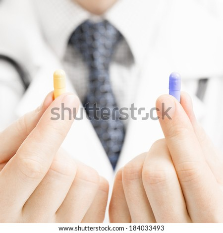 Medical doctor holding one pill in each hand - 1 to 1 ratio