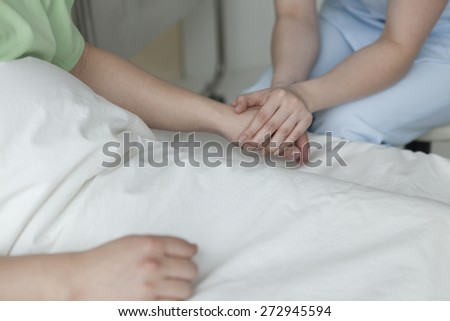 Medical doctor holing patient's hands and comforting his