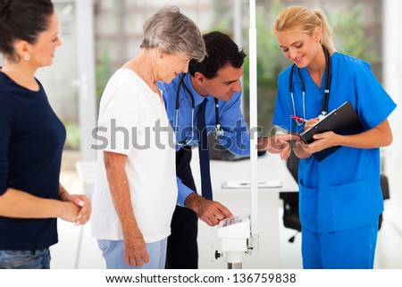 medical doctor monitoring senior patient's weight with his assistant