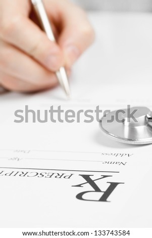 Medical doctor signing prescription - ideas for health care - stock photo