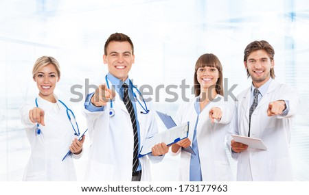 medical doctor team smile with stethoscope point finger at you. Excited happy smiling group of people in hospital, wear white lab coats