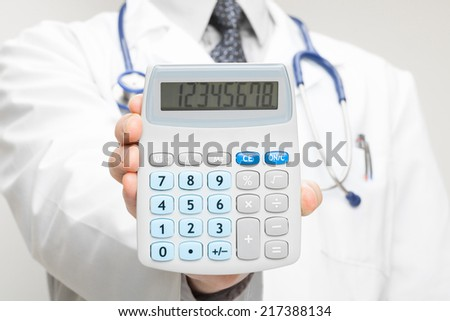 Medical doctor with calculator in his hand - closeup shot - stock photo