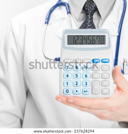 Medical doctor with calculator in his hand - medical aid concept - stock photo