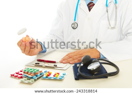 Medical doctor with stethoscope sitting at a desk in his office - stock photo