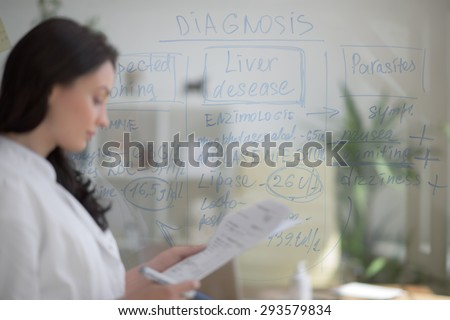 Medical doctor writing patient test results on transparent board to diagnose disease of her patient - stock photo