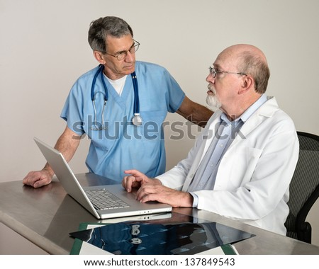 Medical doctors at laptop computer discussing patient's scans. Short depth of field; doctor in background in soft focus.