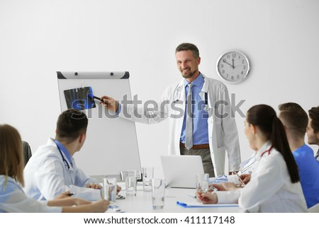 Medical doctors sitting at the meeting in modern hospital - stock photo