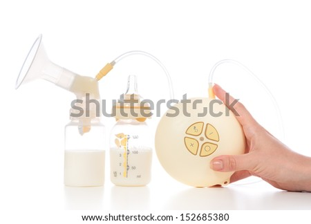 Medical electric breast pump to increase milk supply for breastfeeding mother and bags of frozen breastmilk isolated on white background - stock photo