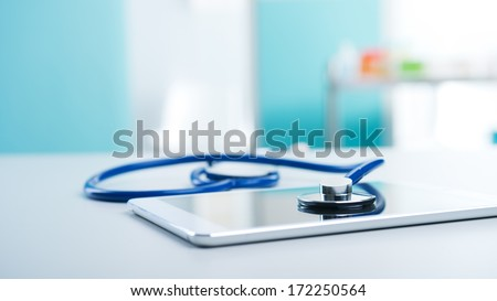 Medical equipment: blue stethoscope and a digital tablet. - stock photo