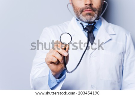 Medical exam. Close-up of mature grey hair doctor examining you with stethoscope while standing against grey background