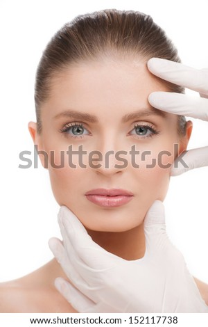 Medical exam. Portrait of beautiful young woman looking at camera while hands in gloves examining her face - stock photo
