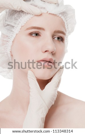 Medical examination face of beautiful woman by hands in glove - close-up portrait isolated on white - stock photo