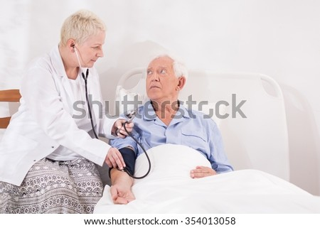Medical examination of senior man lying in bed - stock photo