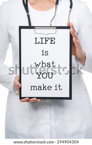 Medical female doctor holding clipboard with a LIFE IS WHAT YOU MAKE IT text written on a sheet of paper. Isolated on white - stock photo