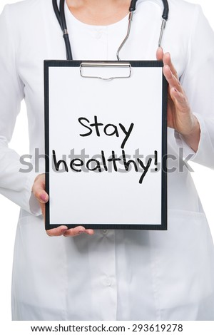Medical female doctor holding clipboard with a STAY HEALTHY text written on a sheet of paper. Isolated on white - stock photo