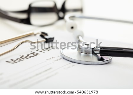 Medical form and stethoscope on white background