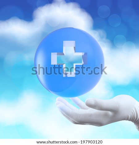 medical hand with globe select on first aid sign as concept - stock photo