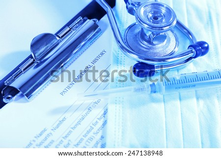 Medical history on clipboard with stethoscope on light background - stock photo