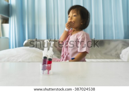 medical in syringe kid background,sick little girl lying on the bed - stock photo
