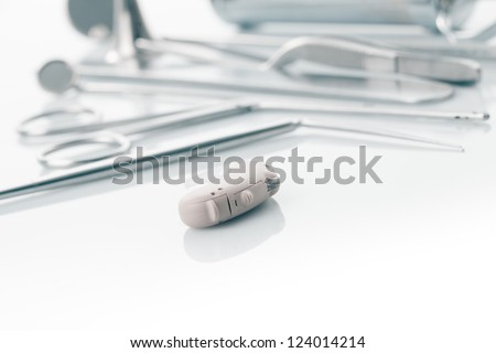 Medical instruments for ENT doctor on white and hearing aid, alternative to surgery - stock photo