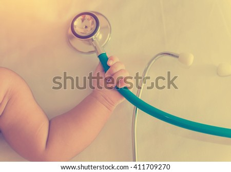 medical instruments stethoscope in hand of newborn baby girl. vintage style - stock photo