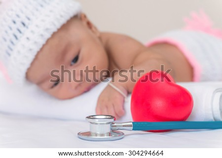 medical instruments stethoscope with heart and baby girl. - stock photo