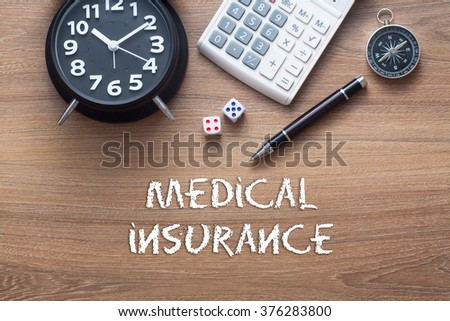 Medical insurance written on wooden table with clock,dice,calculator pen and compass - stock photo